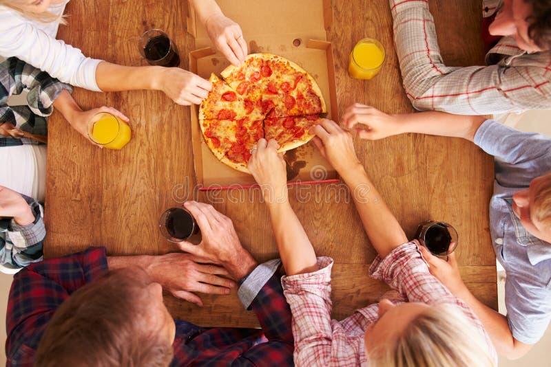 Vänner som tillsammans delar en pizza, över huvudet sikt arkivfoton