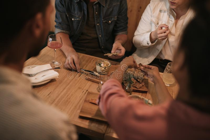 Vänner som tillsammans delar mat i en stång på natten arkivbild