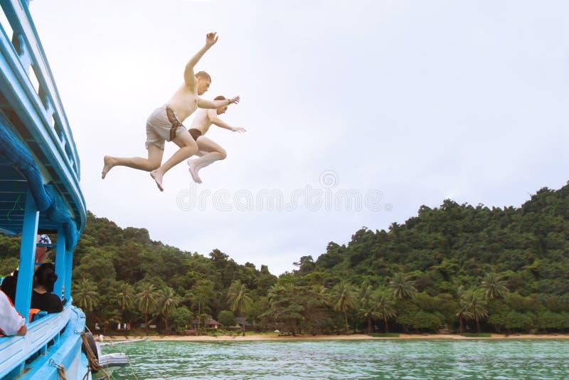 Vänner som tillsammans hoppar till havet från fartyget och att ha gyckel, sätter på land tropisk semester arkivfoton