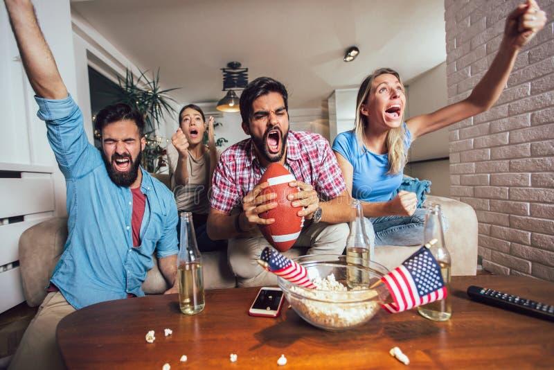 Vänner som tillsammans hurrar sportligan på tv och hemma firar seger royaltyfri fotografi