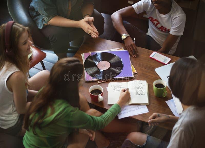 Vänner som tillsammans lyssnar till musik royaltyfria bilder