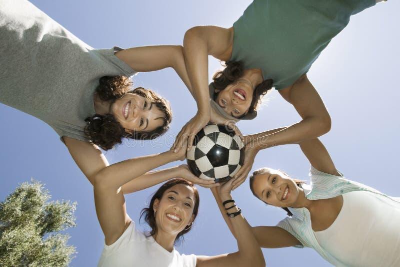 Vänner som tillsammans rymmer fotbollbollen i bråte royaltyfri bild