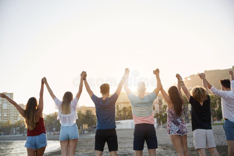 Vänner som tillsammans rymmer och lyfter händer på stranden royaltyfri bild