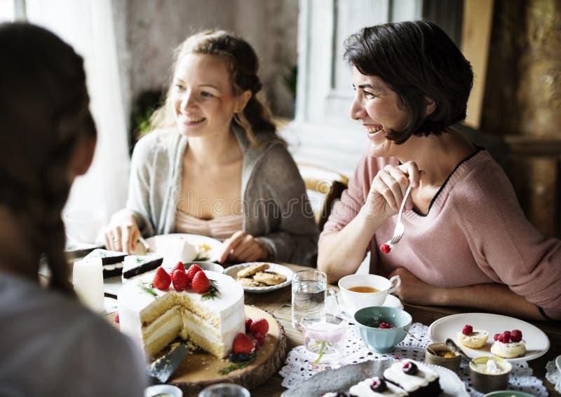 Vänner som tillsammans samlar på tebjudningen som äter kakanjutningH arkivbilder