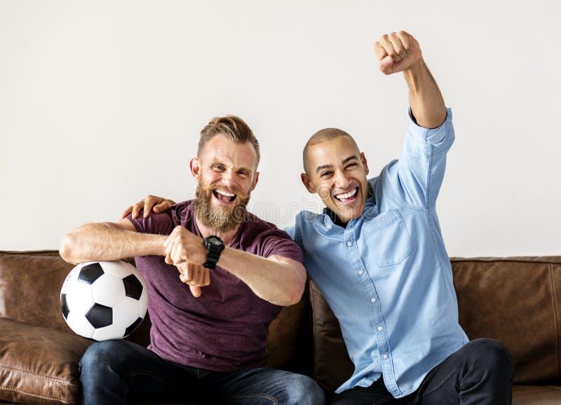 Vänner som tillsammans sitter på en hållande ögonen på sport för soffa arkivbilder