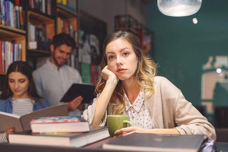 Vänner som tillsammans studerar på coffee shop arkivbild