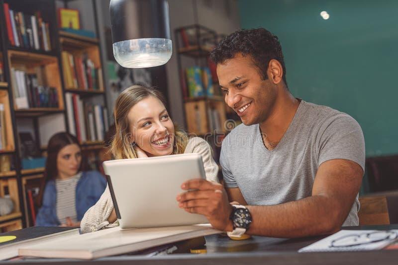 Vänner som tillsammans studerar på coffee shop royaltyfri bild