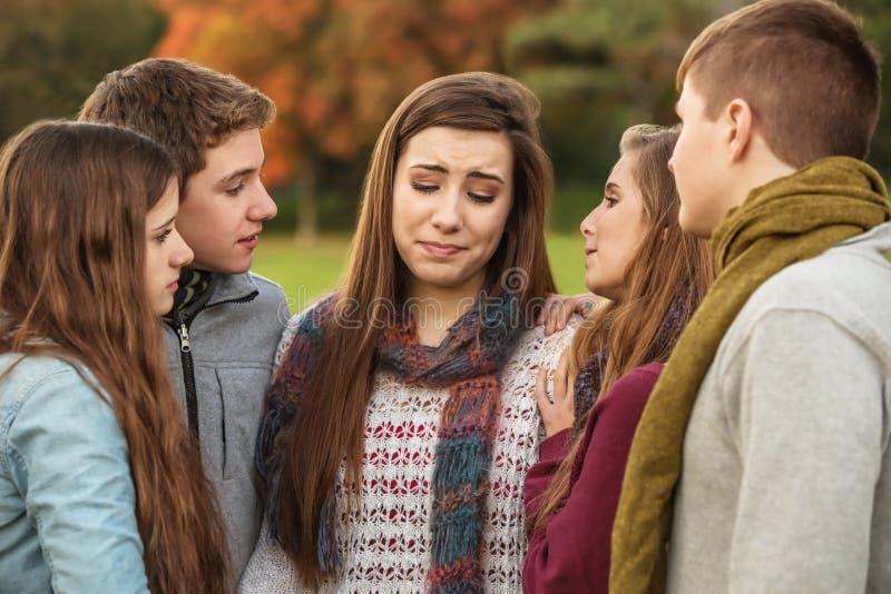 Vänner som tröstar den skriande flickan royaltyfri bild
