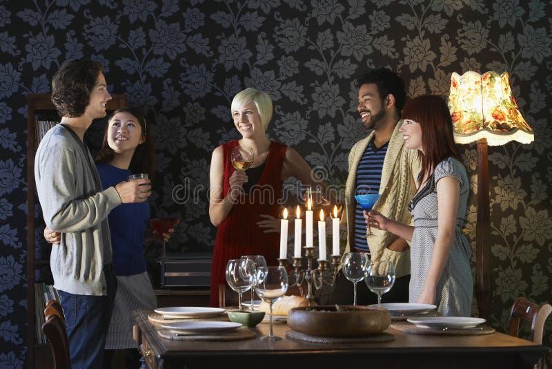 Vänner som tycker om drinkar, genom att äta middag tabellen fotografering för bildbyråer