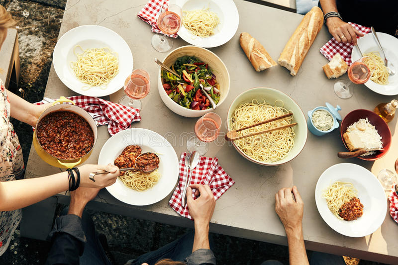 Vänner som tycker om ett mål av spagetti Bolognaise royaltyfri foto