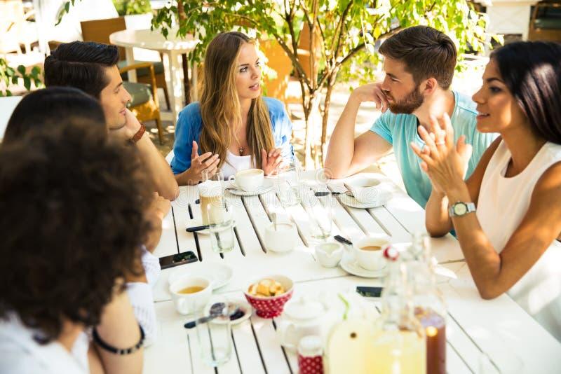Vänner som tycker om mål i restaurang arkivfoto