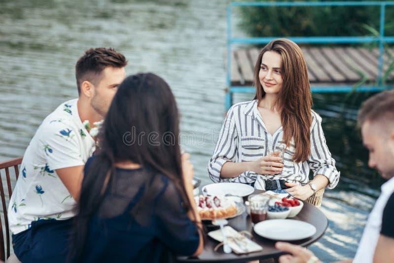 Vänner som tycker om mål under matställen i utomhus- restaurang arkivbilder