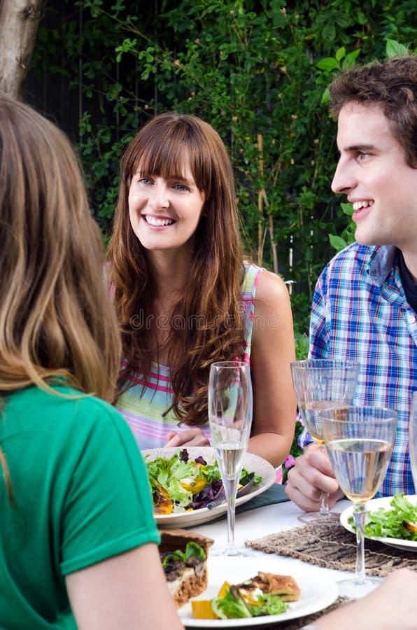 Vänner som tycker om mat och drinkar på en sammankomst royaltyfria bilder