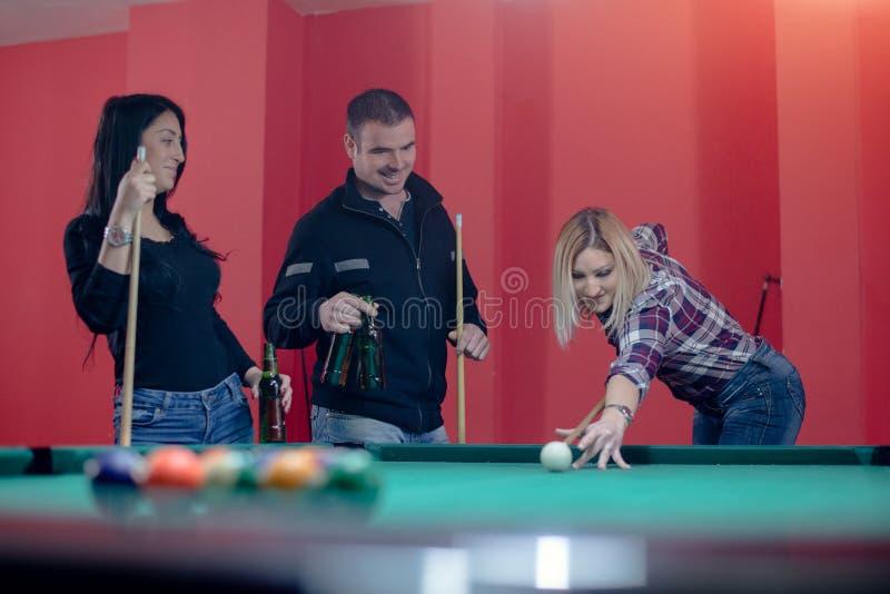 Vänner som tycker om, medan spela billiard royaltyfria foton