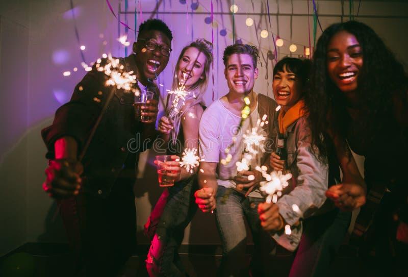 Vänner som tycker om på ett husparti royaltyfri fotografi