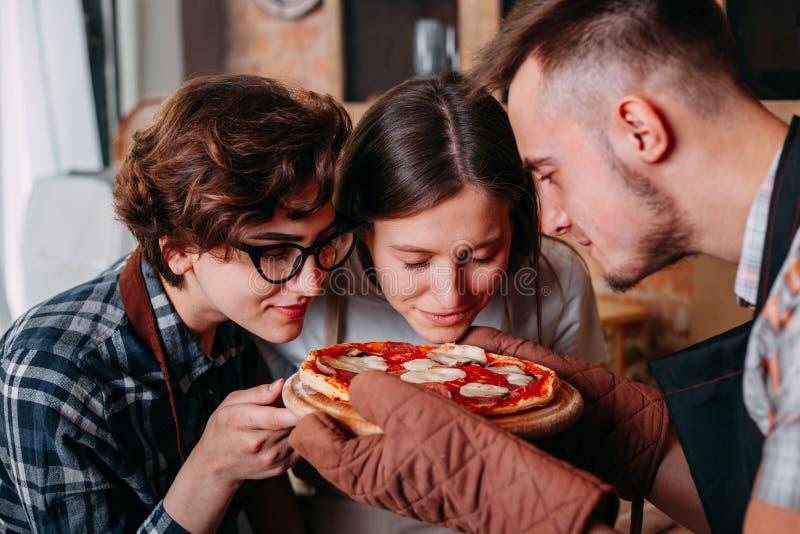 Vänner som tycker om smaklig arom av läcker varm ny bakad pizza royaltyfria bilder