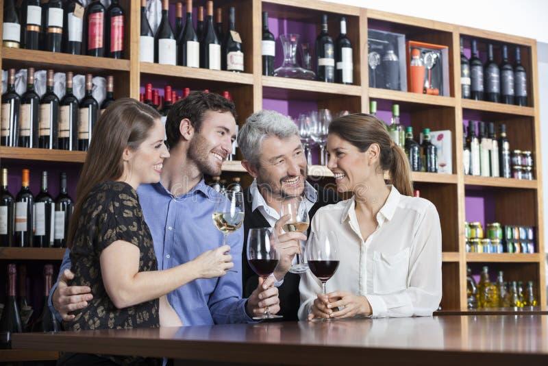 Vänner som tycker om vin på räknaren i vinodling arkivfoton