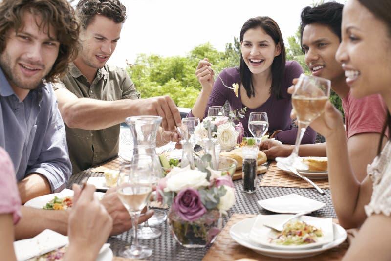 Vänner som utomhus tycker om matställepartiet royaltyfri fotografi