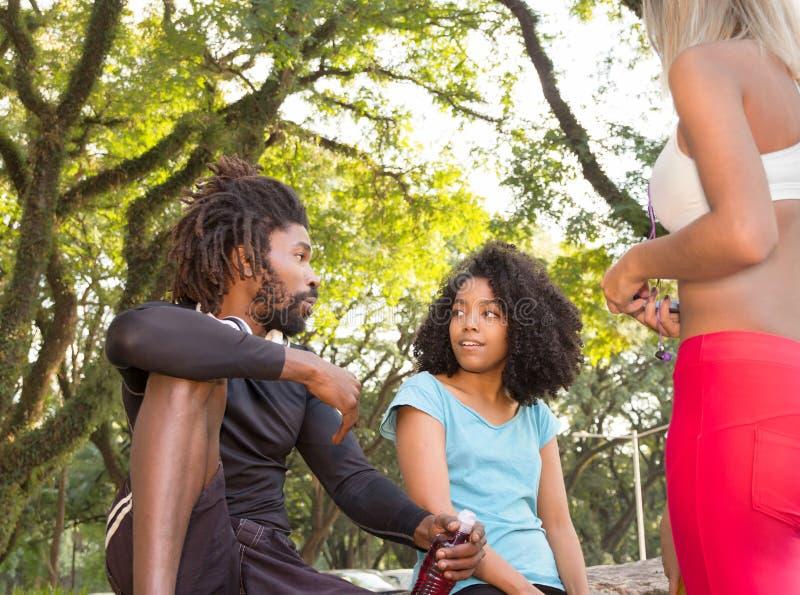 Vänner som utomhus tycker om och talar i skogsmark Sunda Lifes royaltyfri fotografi