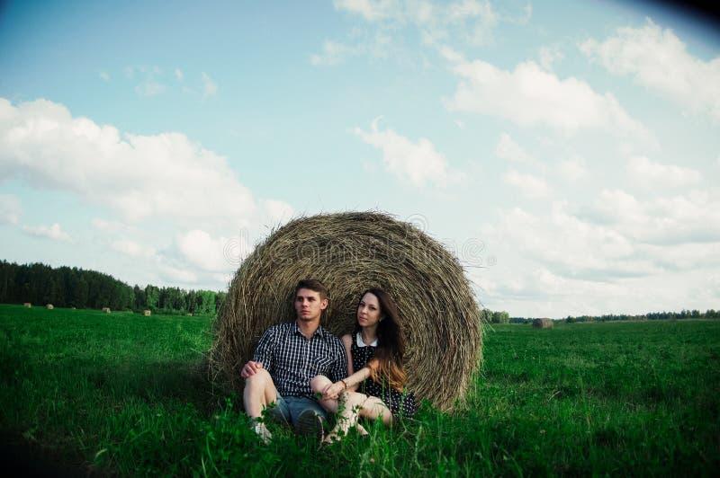 Vänner som vilar i ett fält nära höstackar arkivbild
