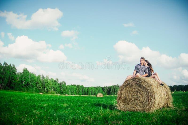 Vänner som vilar i ett fält nära höstackar arkivbilder