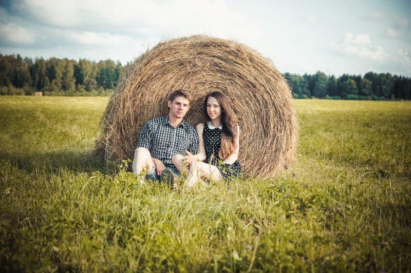 Vänner som vilar i ett fält nära höstackar royaltyfri fotografi