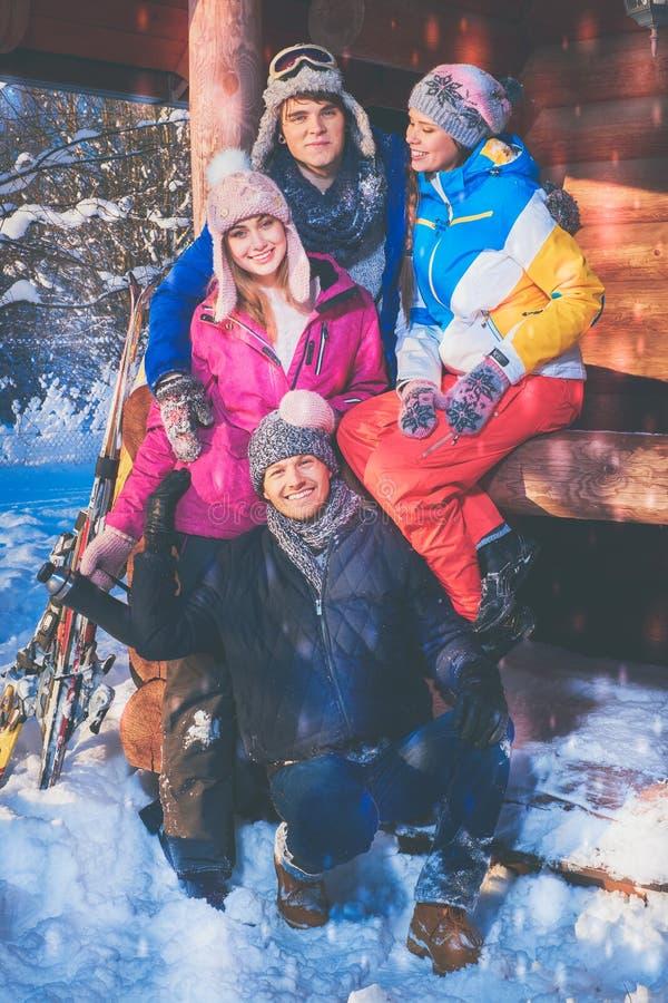 Vänner spenderar vinterferier på bergstugan royaltyfri fotografi