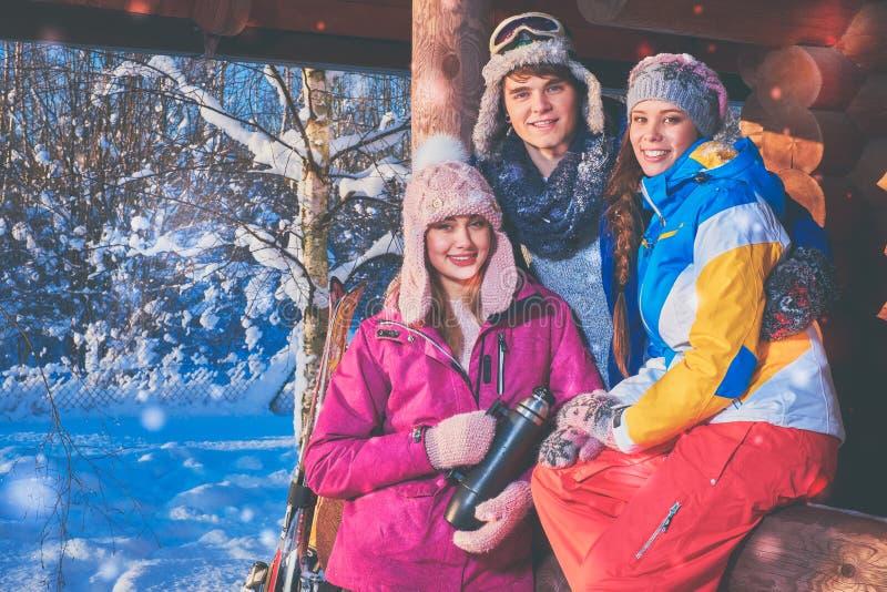 Vänner spenderar vinterferier på bergstugan arkivbild