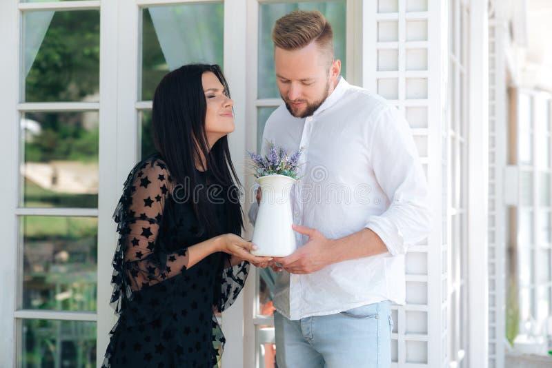 Vänner tar en stark arom av nya blommor, flickan tycker om aromen av en bukett Mannen gjorde en trevlig gåva för royaltyfria bilder