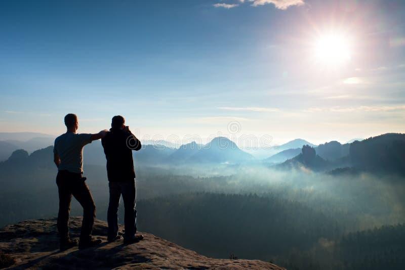 vänner två Att tänka för fotvandrare och fotoentusiasten tar fotostaget på klippan Drömlikt kuflandskap, blå dimmig soluppgång i  royaltyfria foton