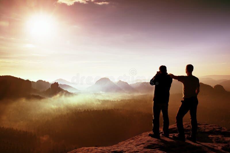 vänner två Att tänka för fotvandrare och fotoentusiasten tar fotostaget på klippan Drömlikt kuflandskap, blå dimmig soluppgång i  arkivbild