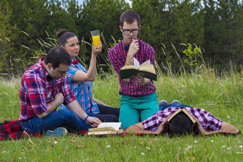 Vänner utomhus med boken royaltyfri fotografi