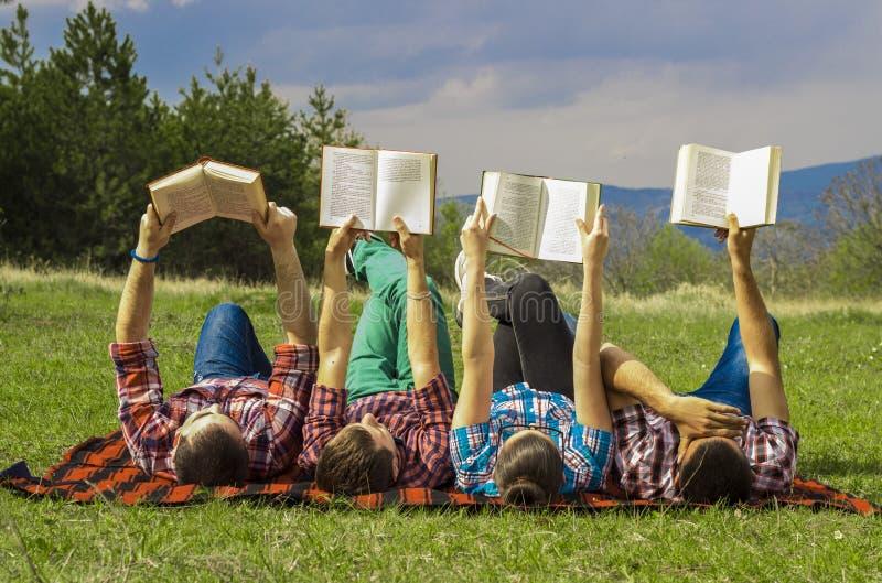 Vänner utomhus med boken royaltyfri bild