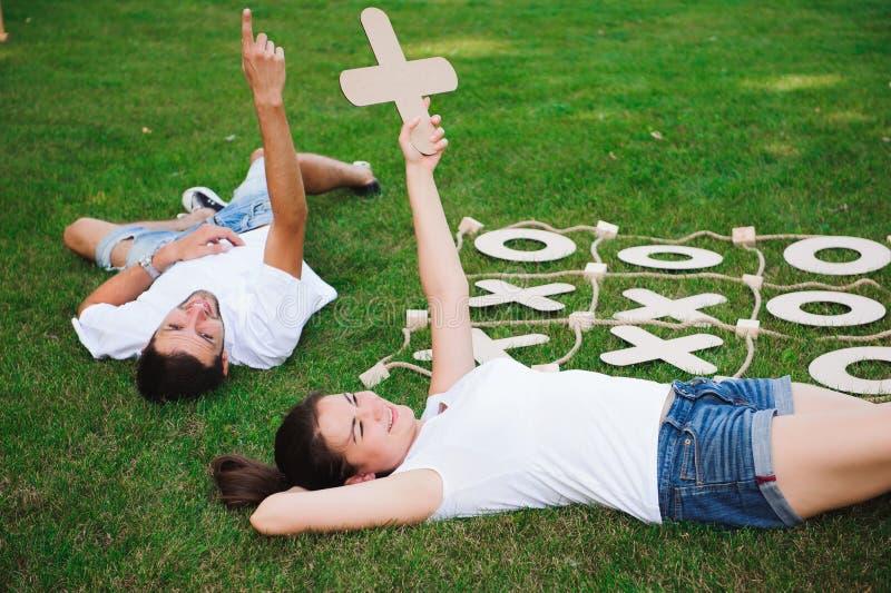 Vänner vilar och spelar muskelryckning-TAC-tån Lek på grönt gräs arkivbilder
