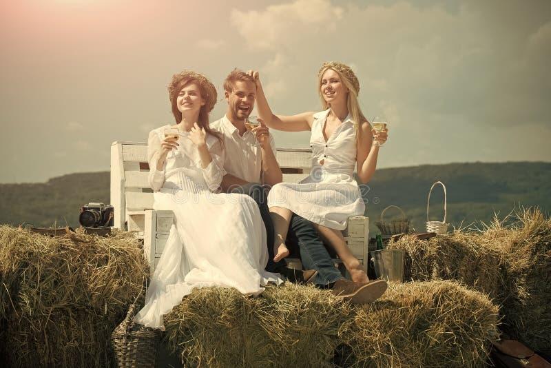 Vänner vilar på naturen Lyckliga vänner som tycker om picknicken på naturligt landskap royaltyfri bild