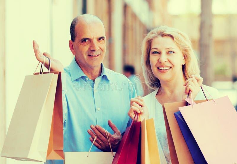 Vänpar, når de har shoppat, turnerar utomhus- le royaltyfria foton