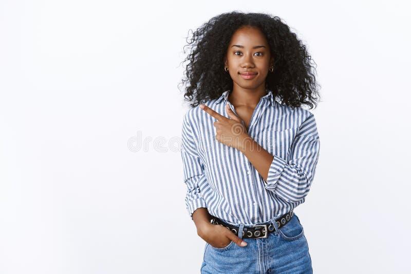 Vänskapsmatch-se den kvinnliga klienten för beslutsam nöjd gladlynt ung afrikansk amerikan som poserar vitt peka för bakgrund royaltyfri bild