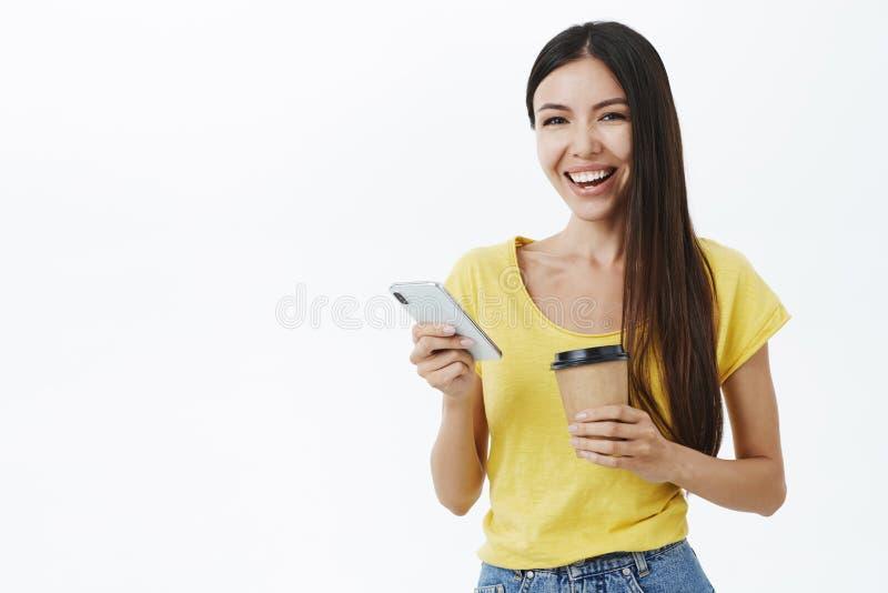 Vänskapsmatch-se glad och underhållen attraktiv europeisk kvinna med långt hår i den moderiktiga gula t-skjortan som rymmer pappe arkivbild