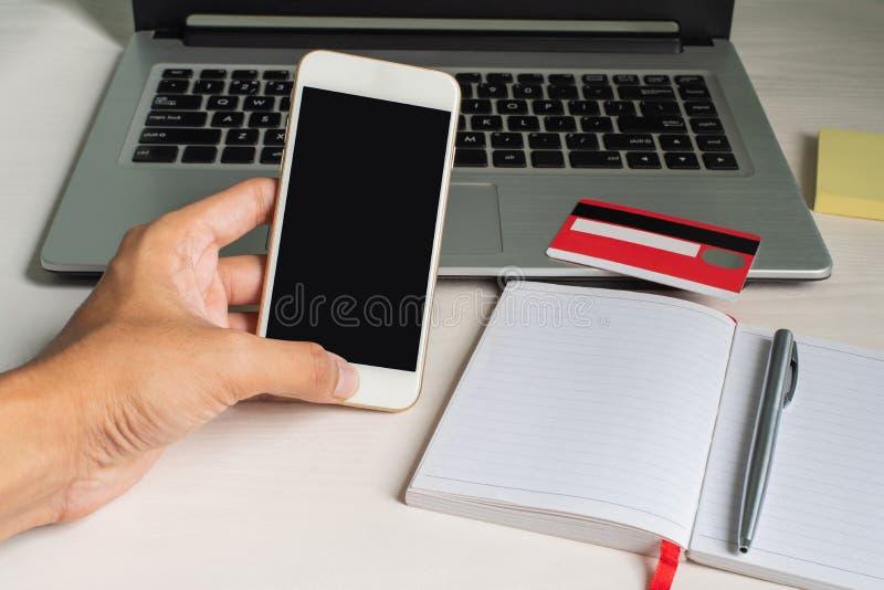 Vänster hand genom att använda smartphonen på blackground med bärbara datorn, dollar, kameran och kreditkorten royaltyfri bild