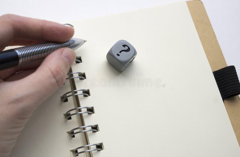 V?nster hand som rymmer en penna ovanf?r en tom sida av en spiral - destinerad anteckningsbok, gr? t?rning med fr?gefl?cken p? de arkivfoto