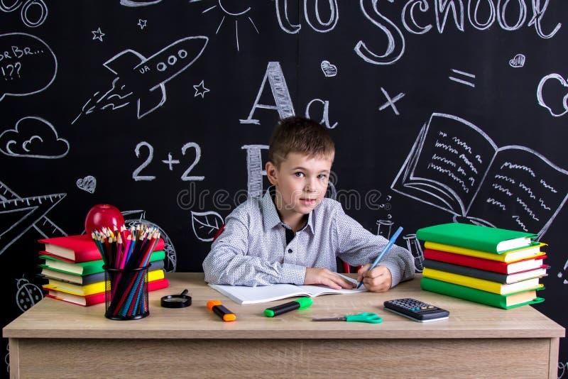 Vänsterhänt skolpojkesammanträde på skrivbordet med böcker, skolatillförsel, handstil i skrivboken som ser rak till royaltyfria foton