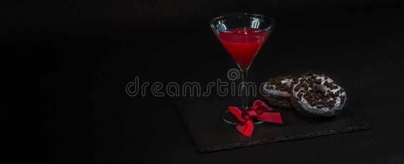 Vänstersidasikten på en drinkkosmopolit per exponeringsglas av martini dekorerade w arkivfoton