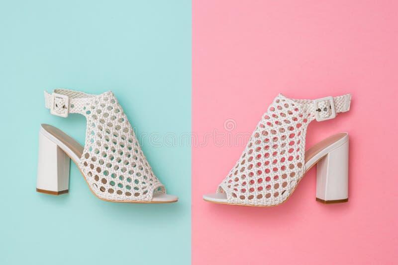 Vänstra och högra sommarkvinnors skor på gränsen av rosa och blåa bakgrunder Lekmanna- l?genhet royaltyfri foto