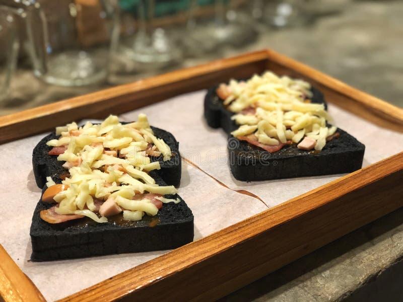 Vänta baka, mini- pizza som göras av kolbröd som överträffas med bacon, och ost royaltyfri fotografi