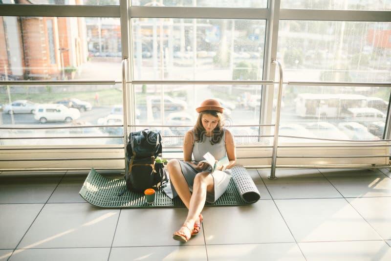 Vänta, försenad transport i terminalen av flygplatsen eller drevstation Den unga caucasian kvinnan i klänning och hatt sitter på  arkivbild