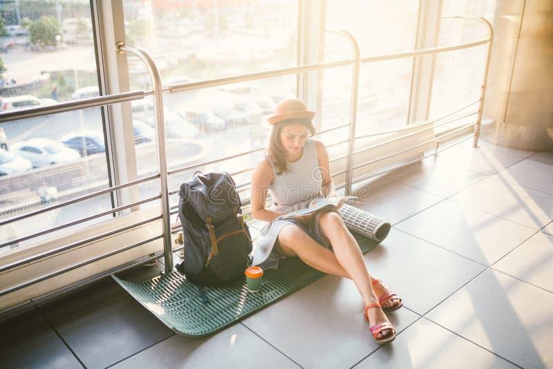 Vänta, försenad transport i terminalen av flygplatsen eller drevstation Den unga caucasian kvinnan i klänning och hatt sitter på  arkivfoto