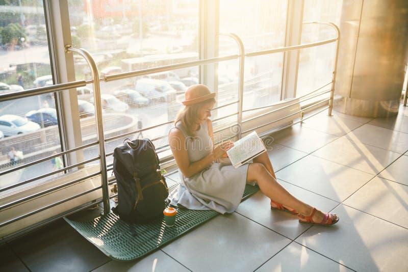 Vänta, försenad transport i terminalen av flygplatsen eller drevstation Den unga caucasian kvinnan i klänning och hatt sitter på  fotografering för bildbyråer
