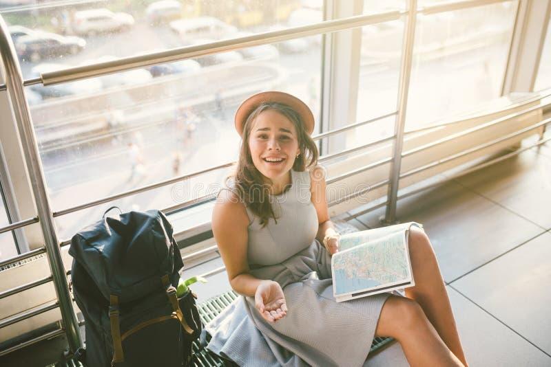 Vänta, försenad transport i terminalen av flygplatsen eller drevstation Den unga caucasian kvinnan i klänning och hatt sitter på  royaltyfria foton