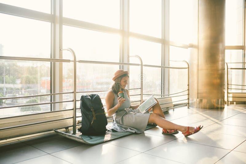 Vänta, försenad transport i terminalen av flygplatsen eller drevstation Den unga caucasian kvinnan i klänning och hatt sitter på  royaltyfria bilder
