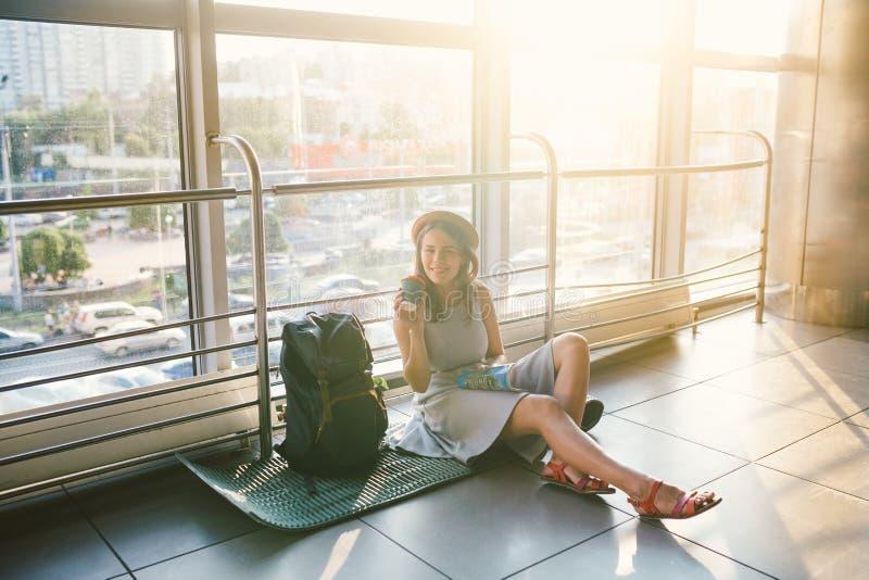 Vänta, försenad transport i terminalen av flygplatsen eller drevstation Den unga caucasian kvinnan i klänning och hatt sitter på  royaltyfri bild